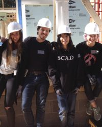 Some of the student volunteers from SCAD Atlanta pose for a picture at the construction site. The students spent more than eight hours helping build the house with Habitat for Humanity. Photo by Gio Turra.